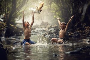 two asian boys playing in a stream