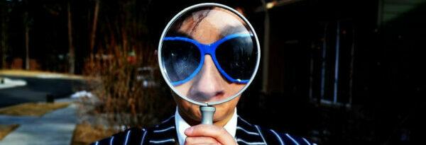 Man looking through magnifing glass