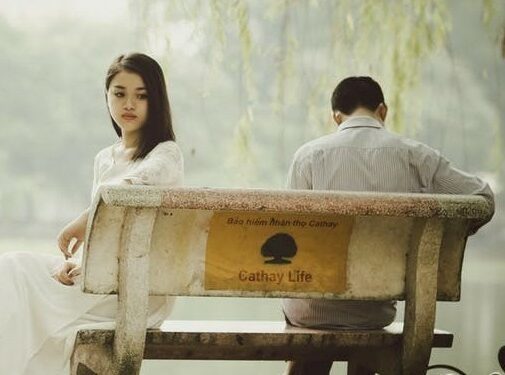 man and woman sitting separated on bench