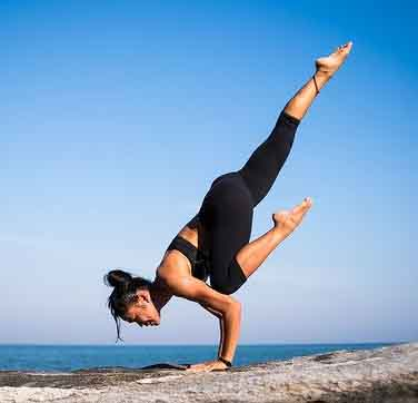 Woman doing difficult yoga pose outside