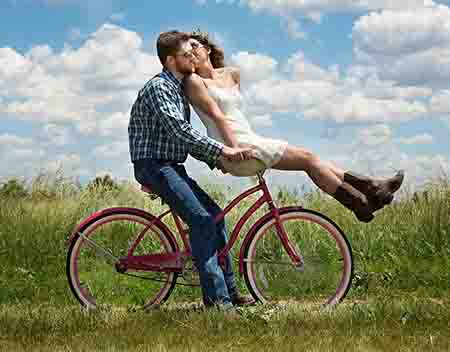 man and women being affectionate while riding a bike