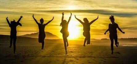 Sihlouttes of happy people jumping in the sunset