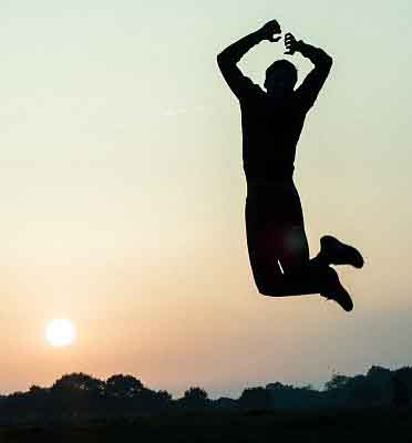Happy man jumping in front of sunset