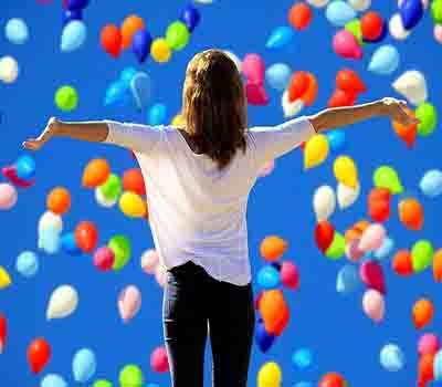 Woman looking at lots of free balloons